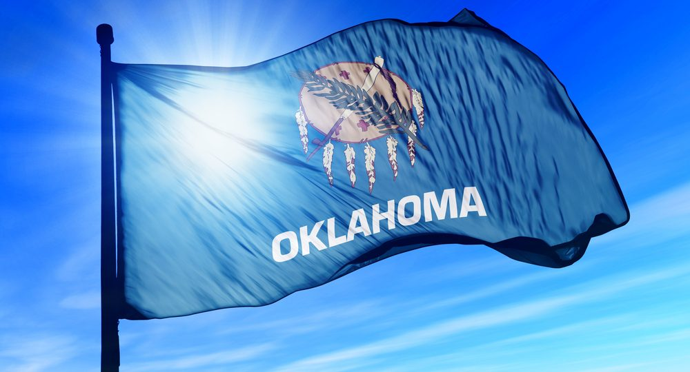 flag of state of Oklahoma against blue sky and sun backdrop