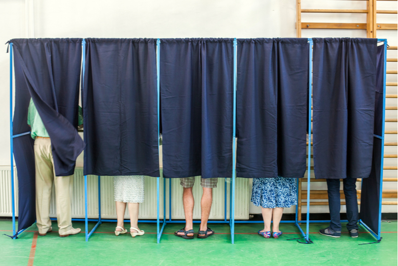 People behind the curtains of a voting booth