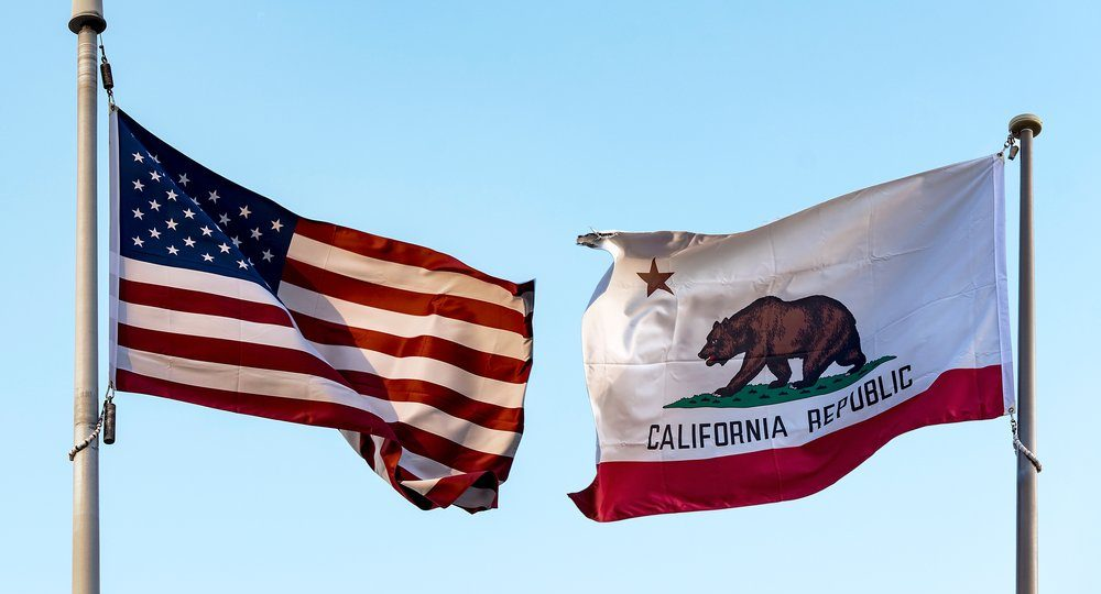 flags of the US and California on masts facing each other