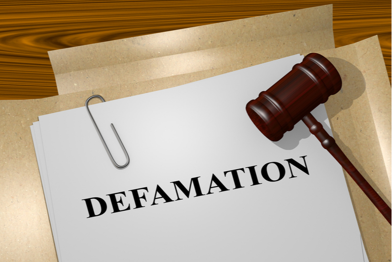 "Gavel next to papers titled ""DEFAMATION"""