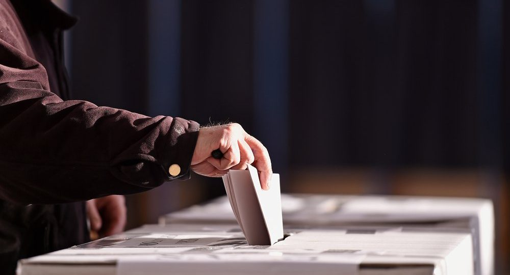 hand placing vote in ballot box
