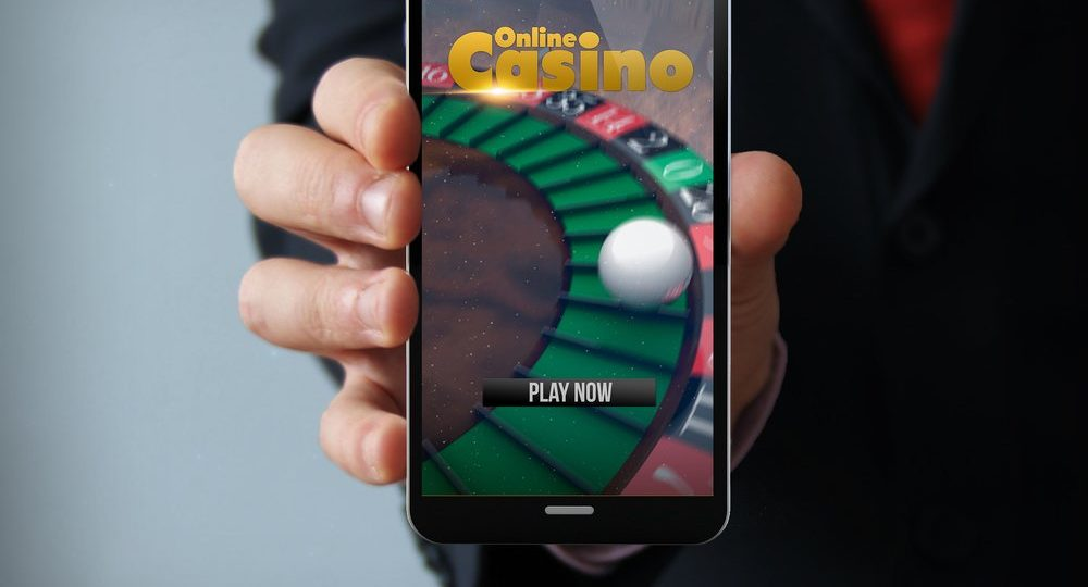 man in suit holding smartphone displaying online casino app